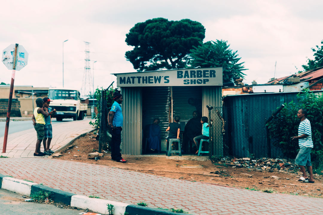 The local barber in Soweto, where an estimated 3-6 million people live, many in simple tin houses.