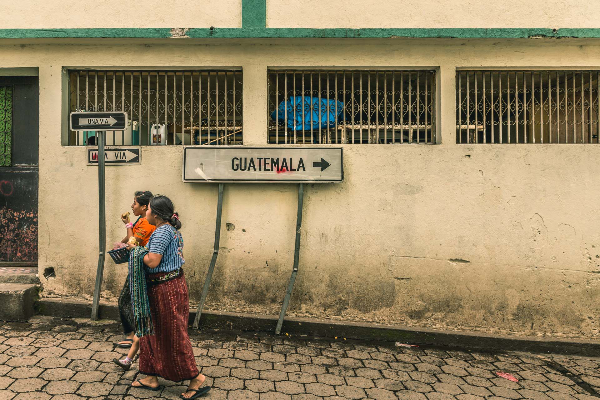 Here two girls are walking away from Guatemala in Santiago by Lake Atitlán.